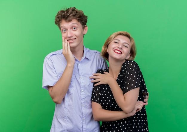 Giovane bella coppia uomo e donna sorridente felice e positivo allegramente in piedi sopra la parete verde