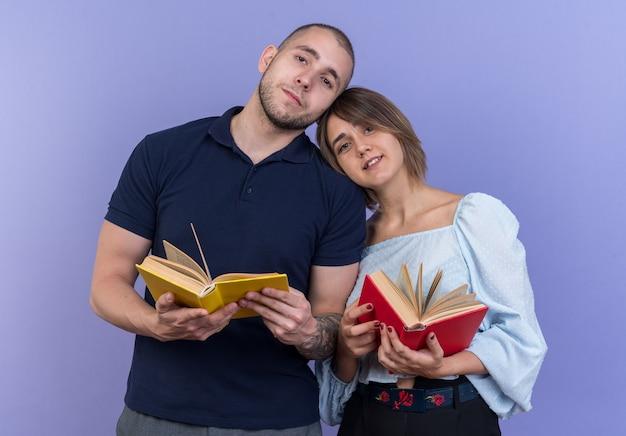 Giovane bella coppia uomo e donna che tiene libri in mano felice e positivo sorridente allegramente in piedi