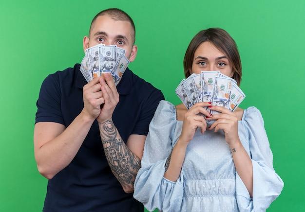 Giovane bella coppia uomo e donna in possesso di contanti che sembrano stupiti e sorpresi in piedi