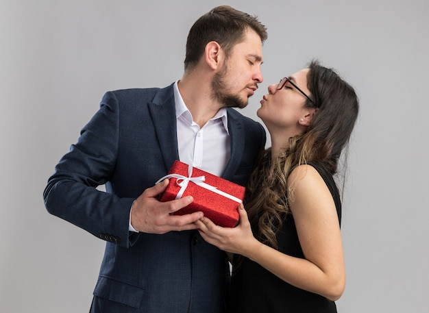 Giovane bella coppia uomo e donna in possesso di un regalo che va a baciare felice in amore festeggiando san valentino