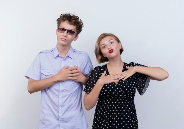 Giovane bella coppia uomo e donna che tengono le mani sul petto sentendosi grati su bianco