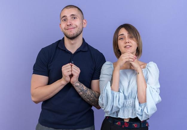 Giovane bella coppia uomo e donna che si tengono per mano insieme sorridendo con l'espressione di speranza in piedi sul muro blu