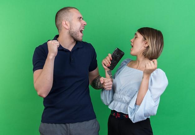 Giovane bella coppia uomo e donna che tiene lo smartphone stringendo i pugni felici ed emozionati che si rallegrano del loro successo in piedi