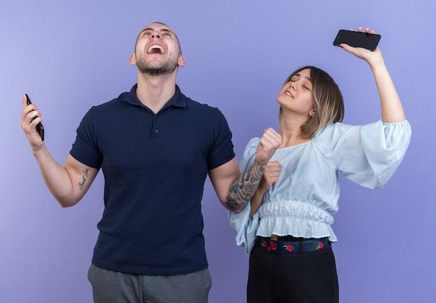 Giovane bella coppia uomo e donna che tiene gli smartphone felici ed eccitati esultando per il loro successo in piedi