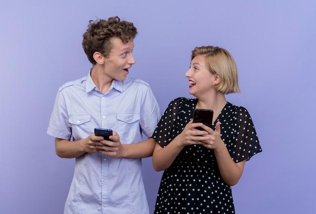 Giovane bella coppia uomo e donna che tengono gli smartphone guardando a vicenda con il sorriso in piedi sopra la parete blu
