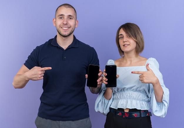 Giovane bella coppia uomo e donna che tiene gli smartphone che puntano con il dito indice ai telefoni sorridendo allegramente felice e positivo in piedi
