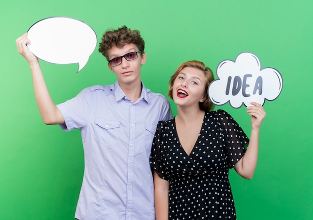 Young beautiful couple man and woman holding speech bubble sign smiling standing over green wall