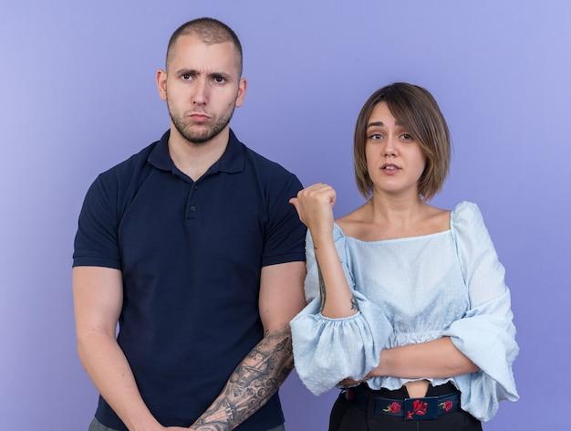 Giovane bella coppia uomo e donna che guarda l'obbiettivo scontento di facce serie donna che punta con il pollice al suo fidanzato in piedi su sfondo blu