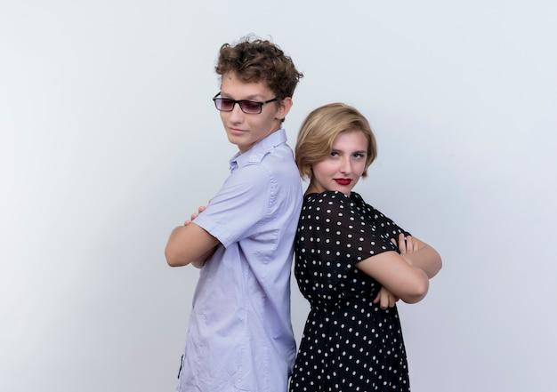 Giovane bella coppia uomo e donna che sembra fiducioso in piedi schiena contro schiena sul muro bianco