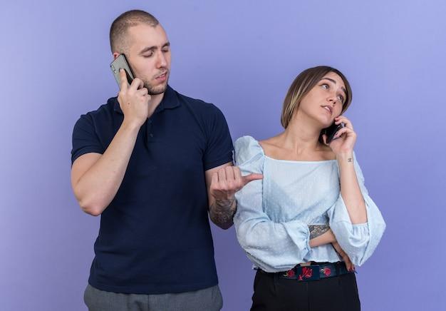 Giovane bella coppia uomo e donna che sembra sicura di parlare al cellulare in piedi