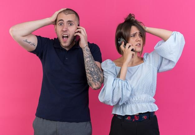 Giovane bella coppia uomo e donna che sembrano confuse e sorprese mentre parlano sui telefoni cellulari in piedi