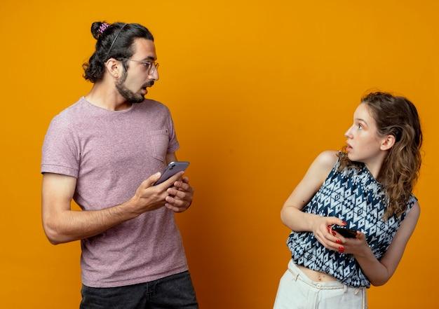 Giovane bella coppia uomo e donna che si guardano con espressione confusa mentre si tengono gli smartphone in piedi sopra il muro arancione