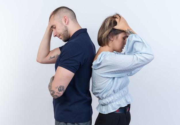 Giovane bella coppia uomo e donna che litigano in piedi schiena contro schiena su muro bianco
