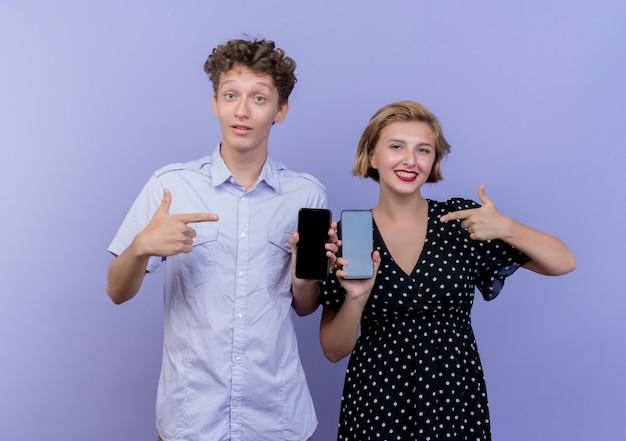 Giovane bella coppia uomo e donna che mostra gli smartphone e pointign con le dita a loro sorridente in piedi sopra la parete blu