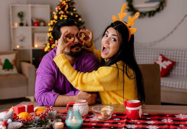 Giovane e bella coppia uomo e donna seduti al tavolo con i biscotti che si divertono insieme felici nell'amore nella stanza decorata di natale con l'albero di natale sullo sfondo