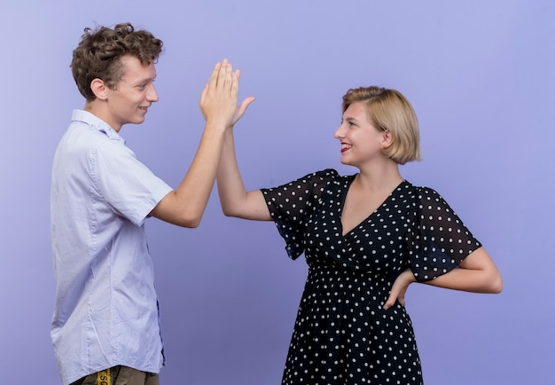 Young beautiful couple man and woman smiling giving high five over blue