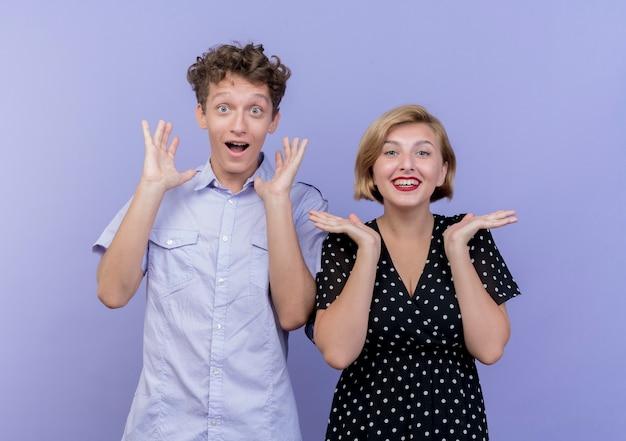 Giovane bella coppia uomo e donna sorridente felice e sorpreso su muro verde