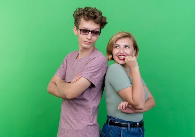 Giovane bella coppia uomo e donna in piedi schiena contro schiena felice e positivo sorridente sul muro verde
