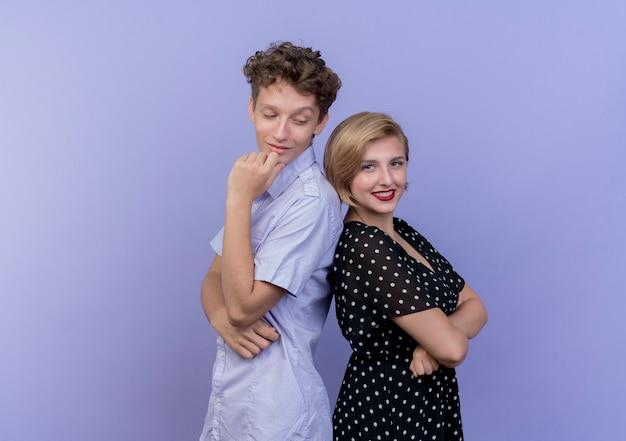 Giovane bella coppia uomo e donna in piedi schiena contro schiena uomo con espressione pensosa sul viso donna sorridente ampiamente oltre il muro blu