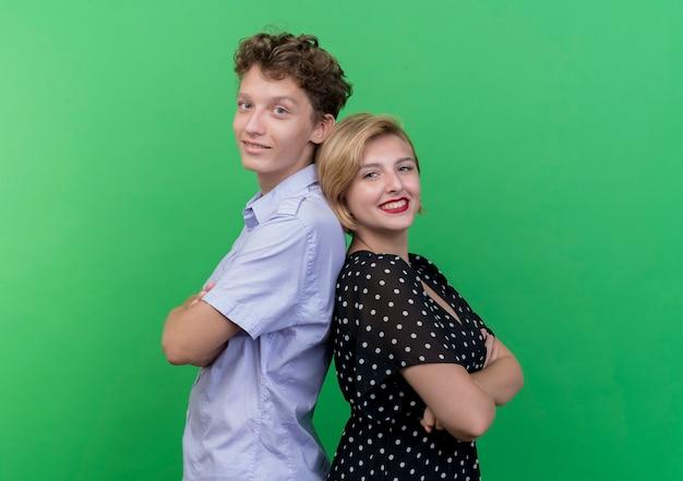 Giovane bella coppia uomo e donna in piedi schiena contro schiena sorridendo ampiamente oltre la parete verde