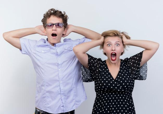 Giovane bella coppia uomo e donna in piedi uno accanto all'altro tenendo la testa scioccata sul muro bianco