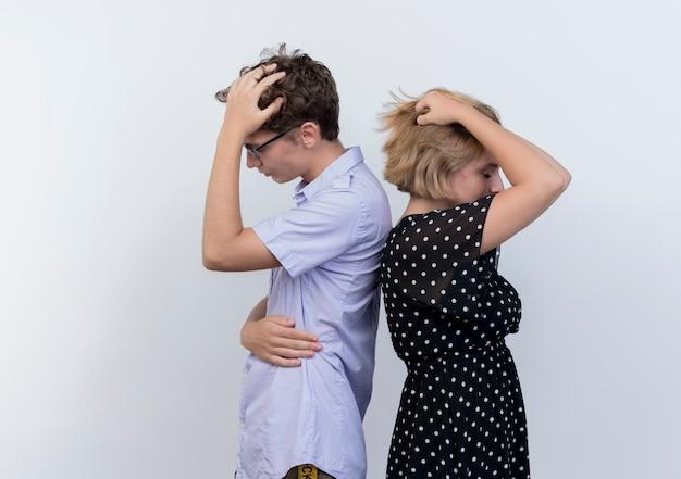 Giovane bella coppia uomo e donna in piedi schiena contro schiena perplessi sul muro bianco