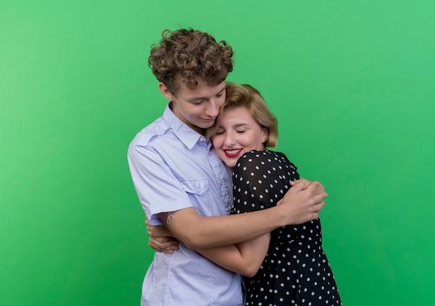Giovane bella coppia uomo e donna in piedi insieme felice nell'amore che abbraccia in piedi sopra la parete verde