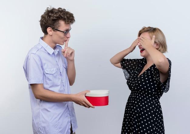 Giovane bella coppia uomo e donna in piedi insieme uomo che fa sorpresa per la sua ragazza mentre lei chiude gli occhi sul muro bianco