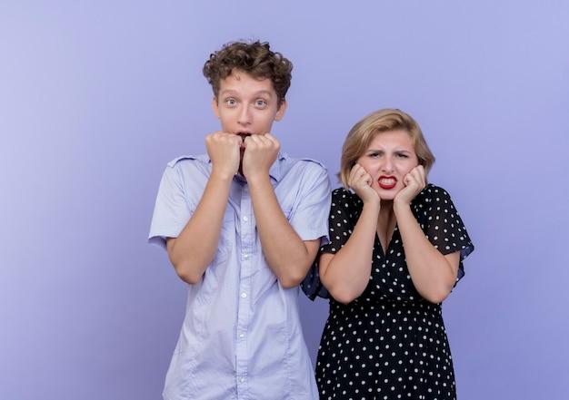 Giovane bella coppia uomo e donna stressati e nervosi nel blu