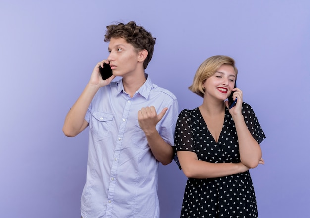 Giovane bella coppia uomo e donna che parla al telefono cellulare in piedi sopra la parete blu