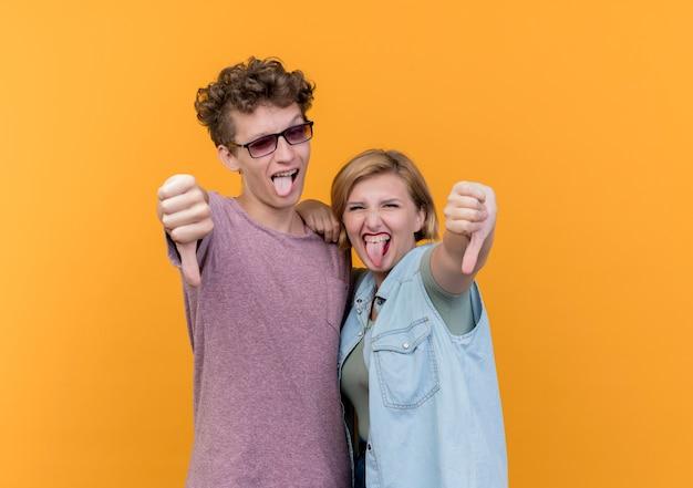 Giovane bella coppia uomo e donna che indossa abiti casual divertendosi insieme che attacca fuori la lingua che mostra i pollici giù in piedi sopra la parete arancione