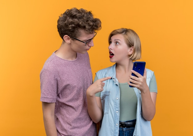 Young beautiful couple man and woman wearing casual clothes man arguing with her girlfriend with smartphone standing over orange wall