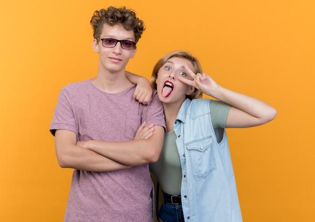 Giovane bella coppia uomo e donna che indossa abiti casual donna che si diverte a sporgere la lingua mostrando segno v in piedi sopra la parete arancione