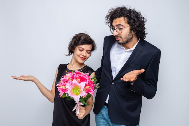 Young beautiful couple man and woman with bouquet of flowers looking confused raising arms celebrating valentine