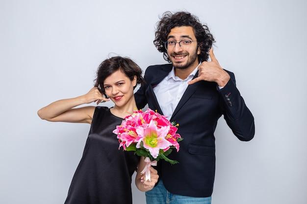 Giovane bella coppia uomo e donna con bouquet di fiori che fa mi chiama gesto sorridendo allegramente felice in amore che celebra la giornata internazionale della donna 8 marzo
