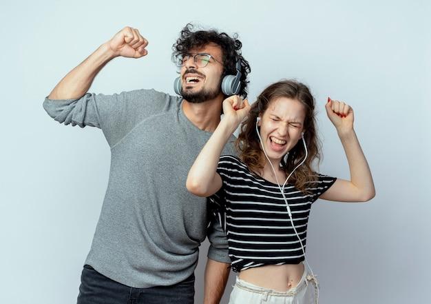 Giovane bella coppia uomo e donna con le cuffie godendo la musica ballare in piedi su sfondo bianco