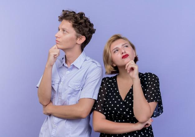 Giovane bella coppia uomo e donna con espressione pensosa sui volti in piedi sopra la parete blu