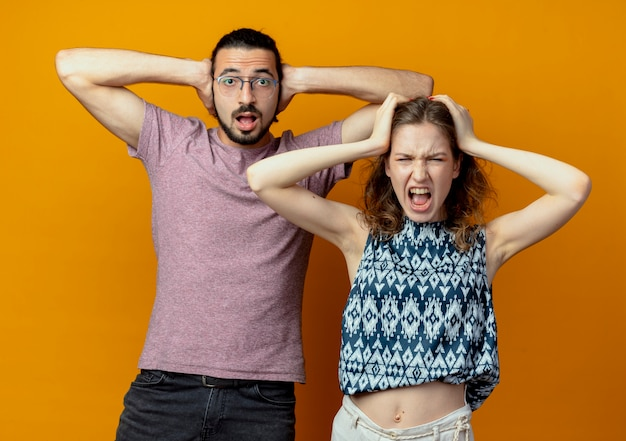 Giovane bella coppia uomo e donna teste toccanti confuse e frustrate in piedi sopra il muro arancione