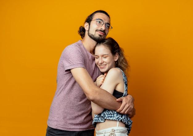 Giovane bella coppia uomo e donna felice nell'amore che abbraccia insieme in piedi su sfondo arancione