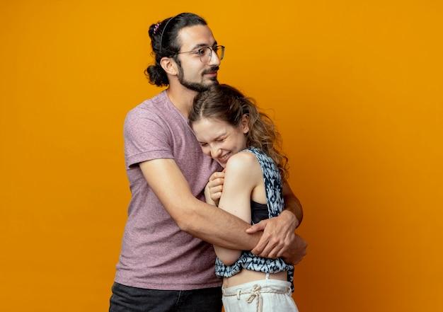 Giovane bella coppia uomo e donna felice innamorato che abbraccia insieme in piedi sopra il muro arancione