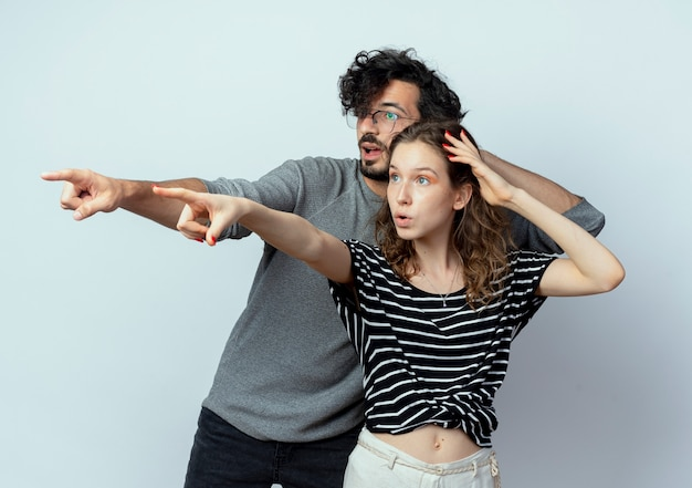 Giovane bella coppia uomo e donna che guarda da parte sorpreso indicando con le dita a qualcosa su sfondo bianco