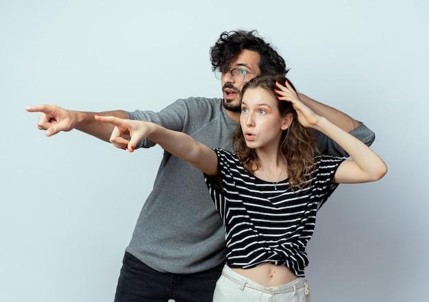 Giovane bella coppia uomo e donna che guarda da parte sorpreso indicando con le dita a qualcosa oltre il muro bianco