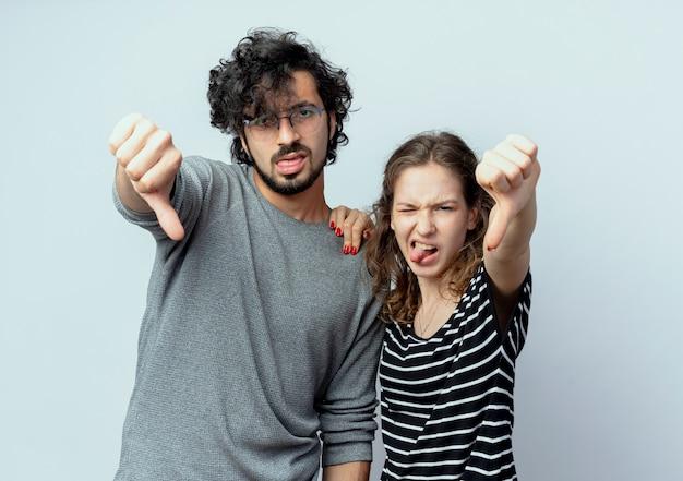 Giovane bella coppia uomo e donna che guarda l'obbiettivo scontento che mostra i pollici verso il basso su sfondo bianco