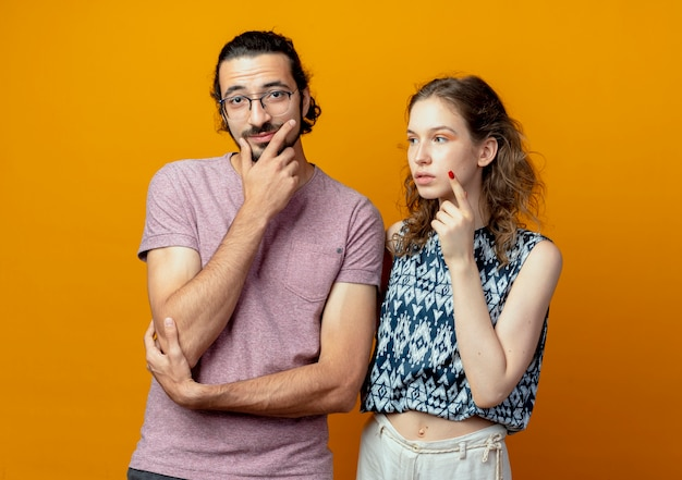 Young beautiful couple man and women looking puzzled thinking standing over orange background