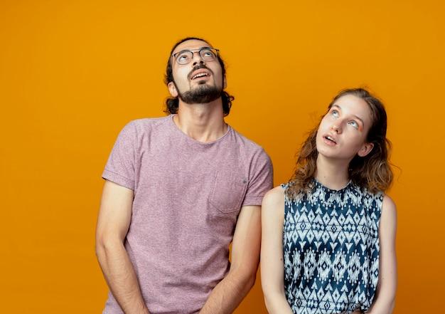 Giovane bella coppia uomo e donna alzando lo sguardo perplesso in piedi su sfondo arancione