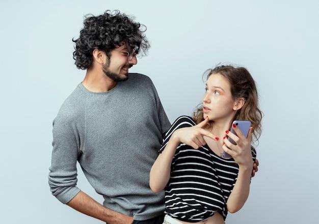Giovane bella coppia uomo e donna, uomo che guarda la sua ragazza confusa che tiene smartphone sopra il muro bianco