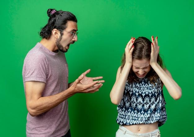 Giovane bella coppia uomo e donna che litigano, uomo che grida alla sua ragazza sconvolta sul muro verde