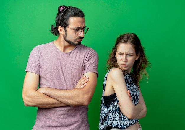 Giovane bella coppia uomo e donna in piedi schiena contro schiena aggrottando le sopracciglia e litigando con le braccia incrociate sul muro verde