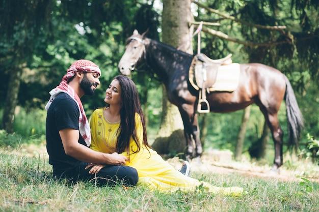 Молодая красивая пара возле черного коня