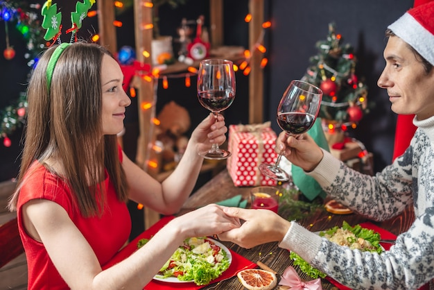 Молодая красивая пара влюбленных проводят праздничный рождественский ужин
